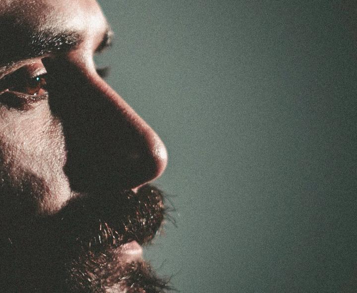 A up close photo of a man's face and beard.