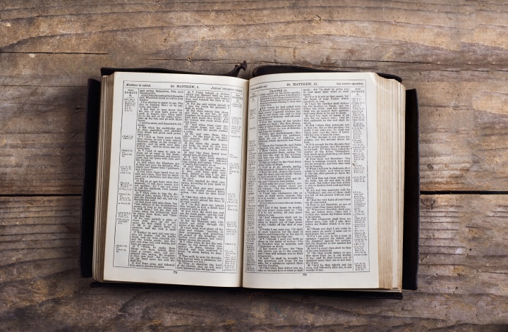 A Bible laying on a table opened to the book of Matthew.