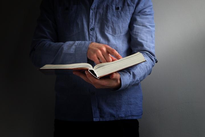 A man holding an open Bible.