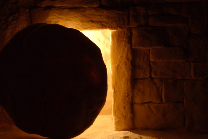 A photo illustration of a tomb with a round stone.