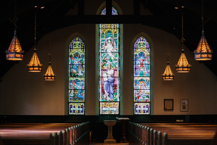 Inside a large church with stain glass windows.