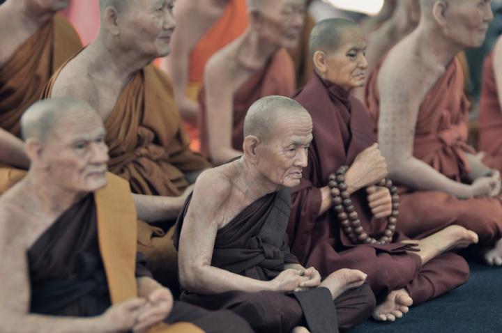 Buddhist monks sitting on the floor.
