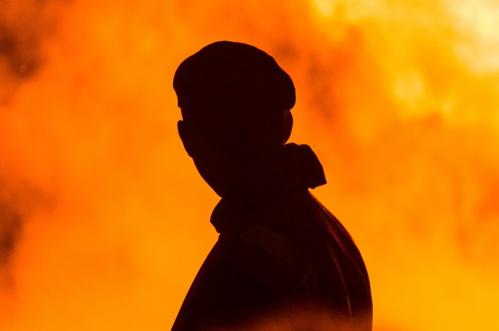 A silhouette of a man with smoke and flames around him.