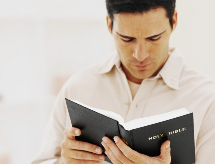 A man holding and reading a Bible.
