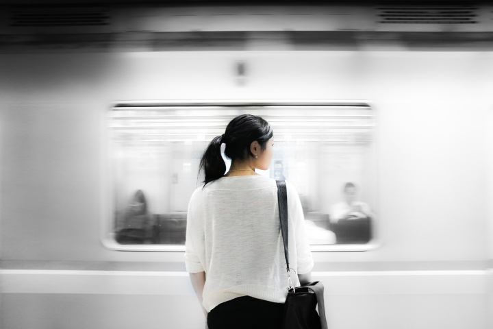A woman standing has a train speeds by.