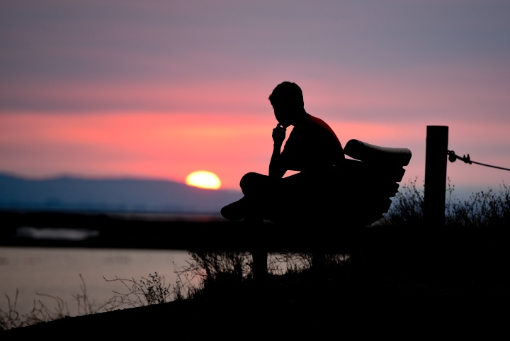 A person sitting on a bench with the sun setting.