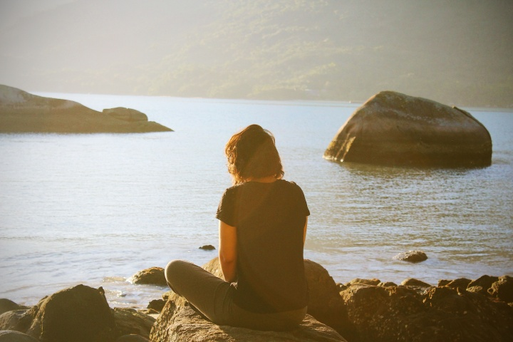 A woman sitting by a body of water.