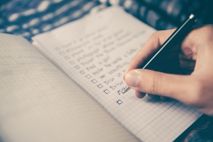 A person making a list with checkbox on paper.