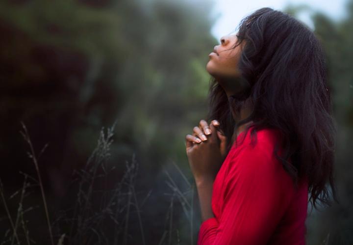 A woman praying while outside.
