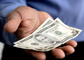 A man holding a $5 dollar bill.