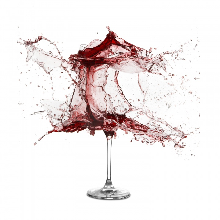 A wine glass exploding with wine.