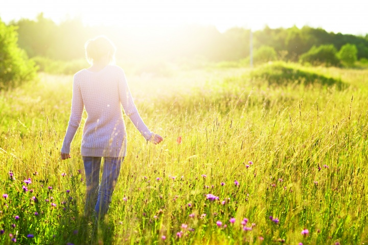 A woman walking in field of tall grass and flowers as sun rays shine on her.