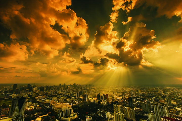 Sun rays shining through clouds on a city.