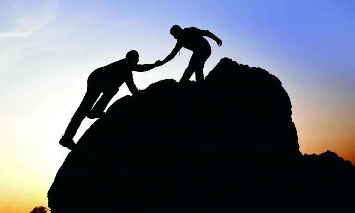 Silhouette of a person helping another person climb a boulder.