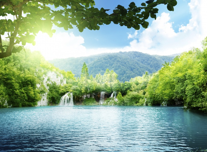 A tropical setting of a lake and waterfalls.