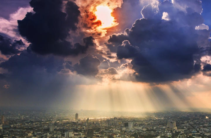 Sun rays and clouds over a big city.