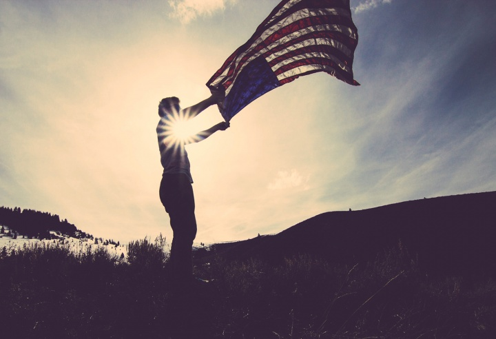 A man holding an American flag flapping in the wind.
