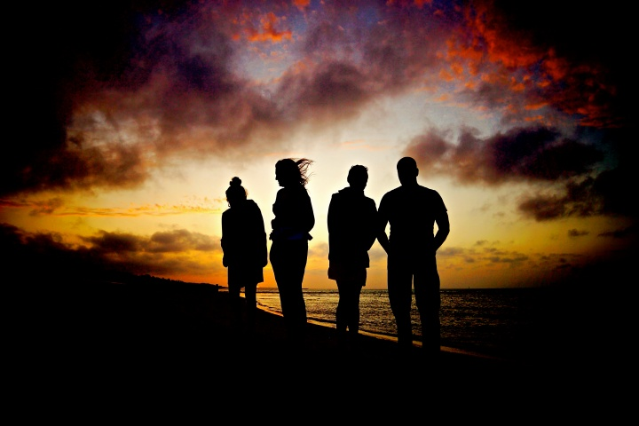 A silhouette of four people at dusk near a body of water.