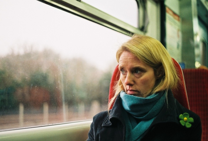 A woman sitting in a train looking out the window.