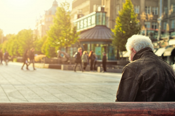 An old man sitting on a park bench looking down.