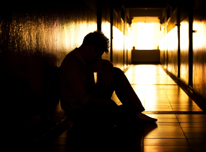A person sitting with the head down in a dark hallway.