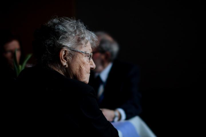A elderly woman sitting by herself.