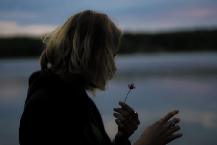 A woman holding a wilting flower in her hand.