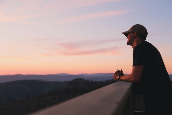 A young man watching the sun set from an observation deck.