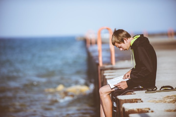 A young man reading a Bible while sitting on a dock.