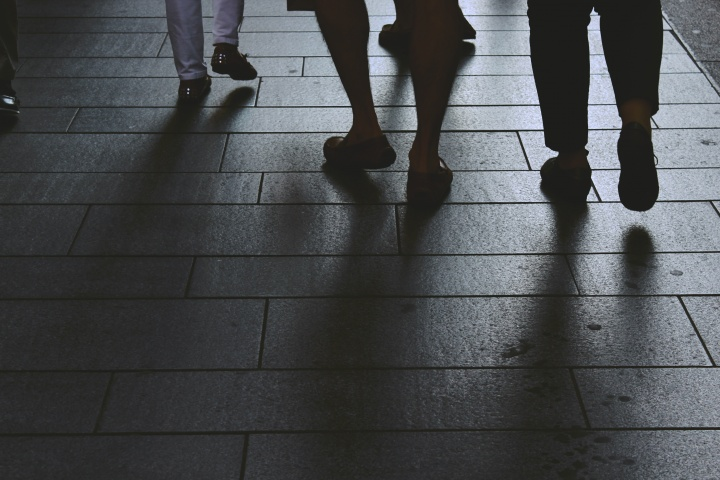 People walking a sidewalk. All you see is their legs and feet.