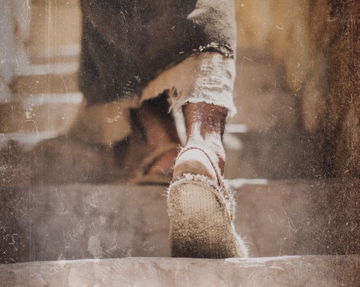 A person wearing sandals walking about dusty steps.