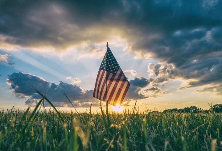 A small United States flag in the grass with the sun setting in the horizon.
