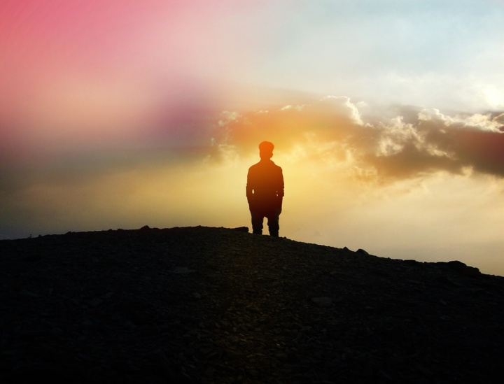 A person standing of top of a hill.
