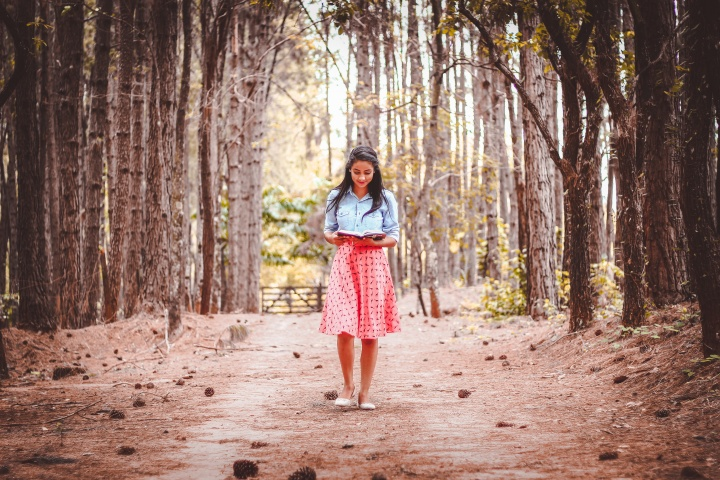 A young woman reading a book while walking on path lined by trees.