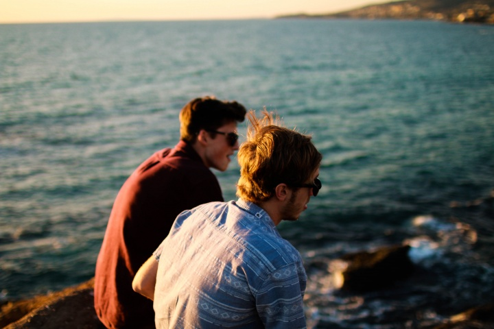 Two young men talking to each other by the ocean.