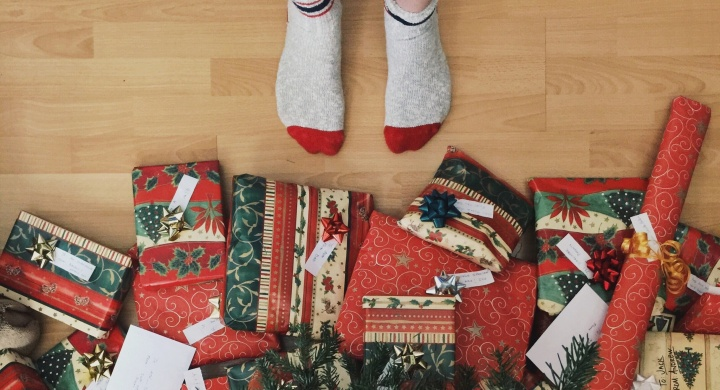 A person with socks standing right beside Christmas gifts.
