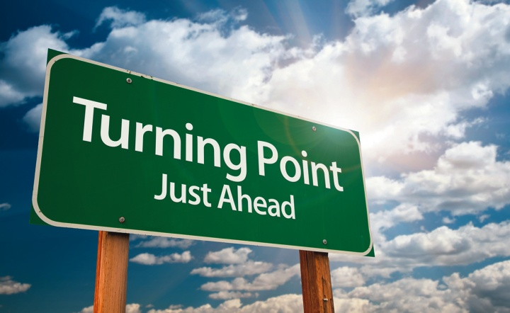 "A green road sign with the words ""Turning Point: Just Ahead""."