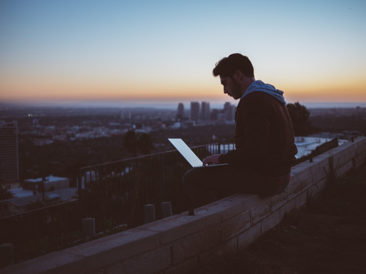 A young man sitting on the edge of wall with a laptop on his lap.