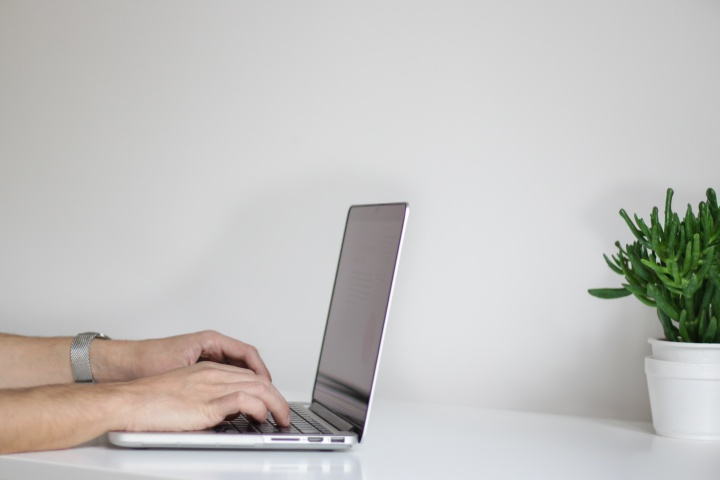 A man typing on a laptop computer.