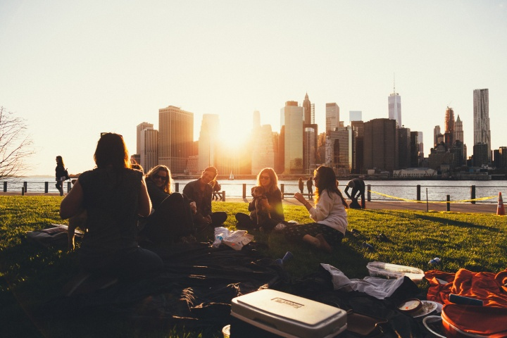 A group of friends on blanket in a park talking.