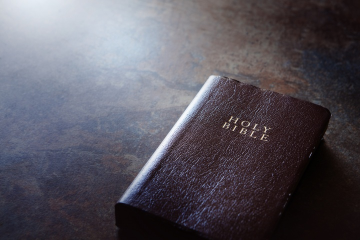 A Bible laying on a brown table.