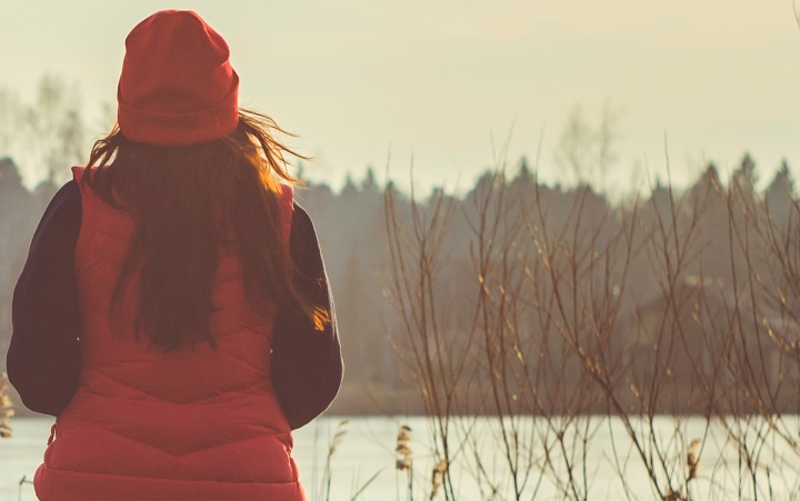 A woman wearing a jacket sitting outside looking at a lake.