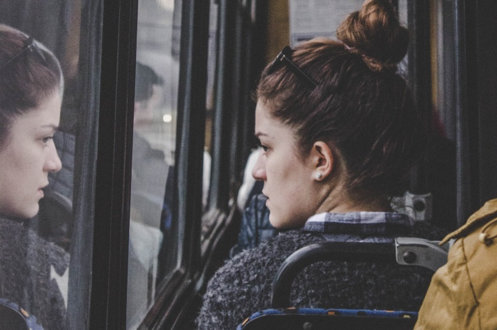 A young woman riding a bus and looking out the window.