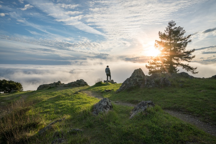 A man standing on top of hill with the sun in the background.