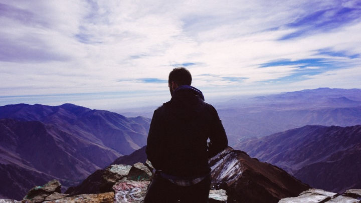 A man standing on top of a mountain peak.