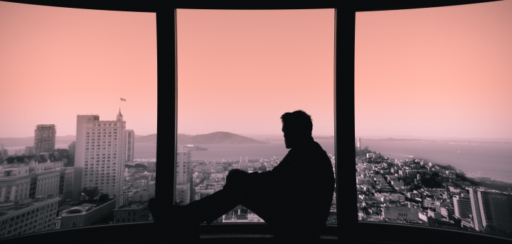 A man sitting in a window sill looking out over a city skape.