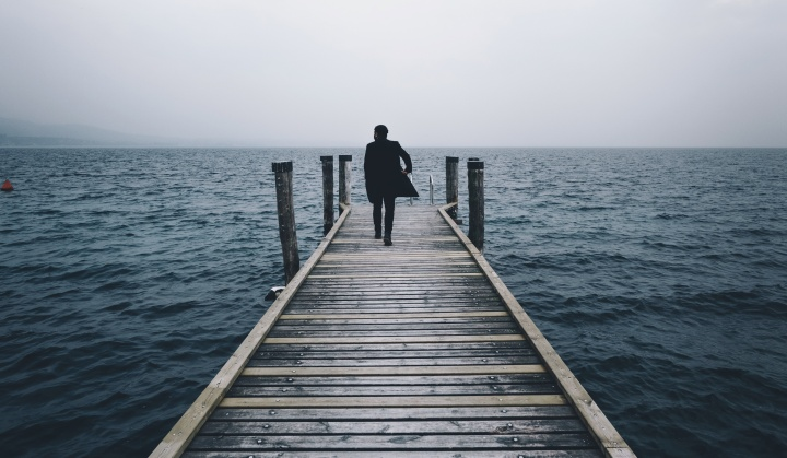 A man walking on a pier going out into the water.