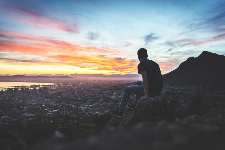 A young man sitting on a rock looking at the cityscape below.