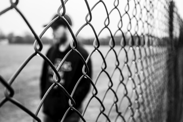 A man standing behind a fence.