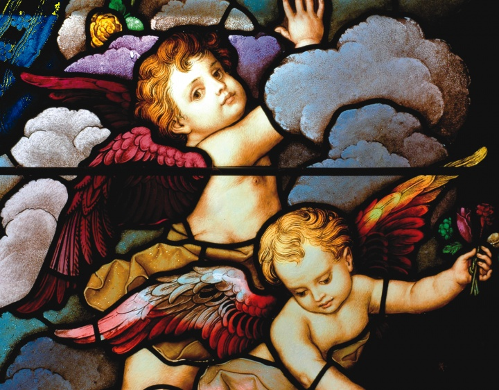 Stained glass close-up of two cherubic angels in the sky